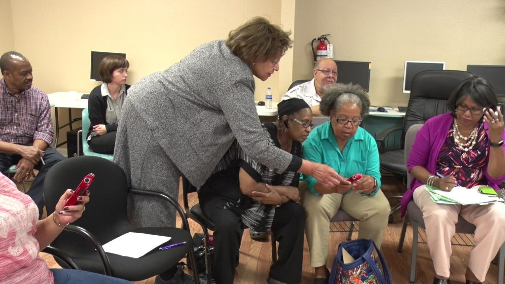 Bernetiae leans over a group of seated African American women to assist them during a training.