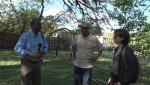 Two African American men and a white woman stand beneath tree branches and blue sky at Griffin Cemetery. One of the men, on the left is holding a microphone.