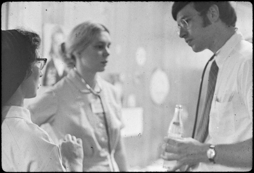 a photograph from the 1960s of a young doctor (on the right) consulting with a nursing student (left background) and nun (left foreground) in a hospital