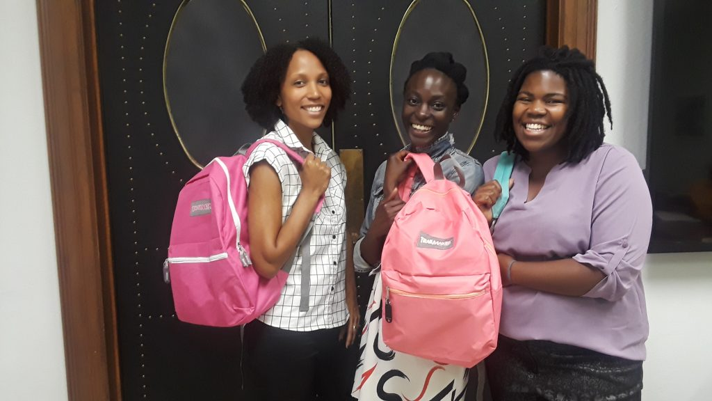 Three African American women stand smiling while carrying and holding pink Archivist in a Backpack kits