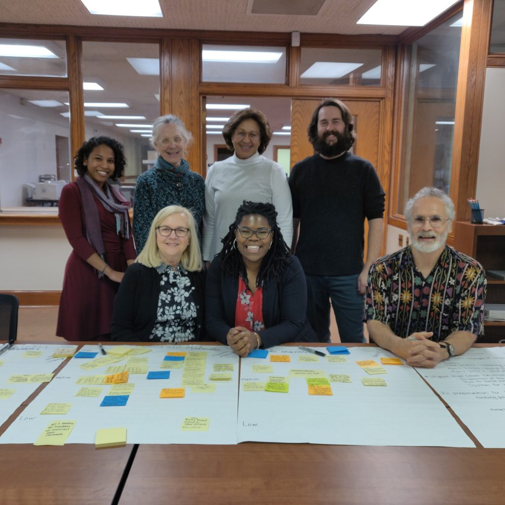 Three members of the Student Health Coalition smile with members of the CDAT. On the table in the foreground are large sheets of paper with colorful sticky notes