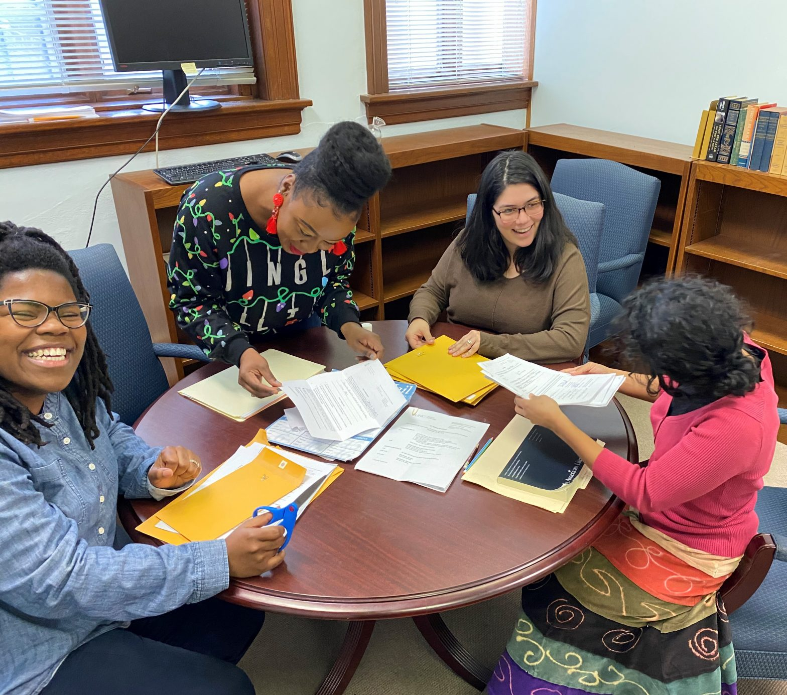 Chaitra Powell, Charlissa Rice, Sonoe Nakasone, and Alex Paz Cody gather around a table to create information packets for incoming Archival Seedlings