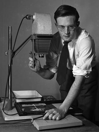Hugh Morton standing next to an enlarger.