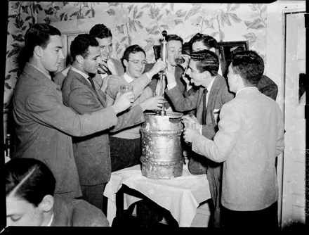 Group of male UNC-Chapel Hill students eagerly surrounding beer keg, possibly at the DKE Fraternity House, ca. 1940-1942