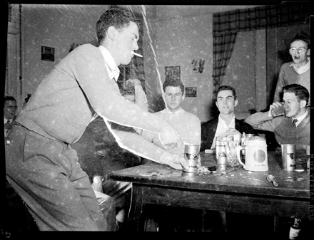 UNC-Chapel Hill student opening a Budweiser beer can which is spewing foam while other students look on, possibly at the DKE Fraternity house, ca. 1940-1942