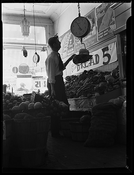 Dan Martin weighing produce in a Chapel Hill grocery, circa 1942.