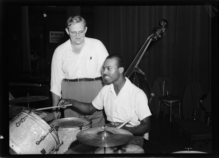 Unidentified jazz drummer, circa 1940s-early 1950s, with man (bass player?) looking on
