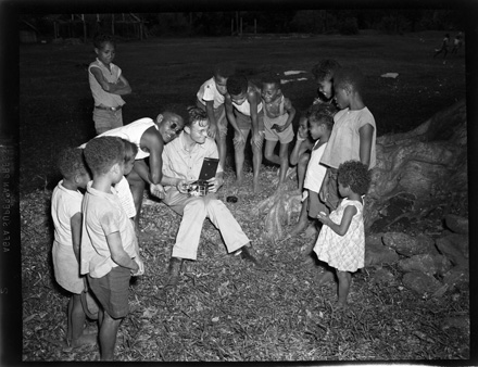 Hugh Morton showing his movie camera to some Pacific island children, possibly at Bougainville, during World War II (early 1940s)