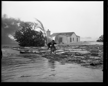 Julian Scheer wading through debris after Hurricane Hazel (1954)