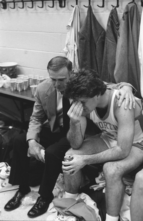 UNC men's basketball player being consoled in locker room