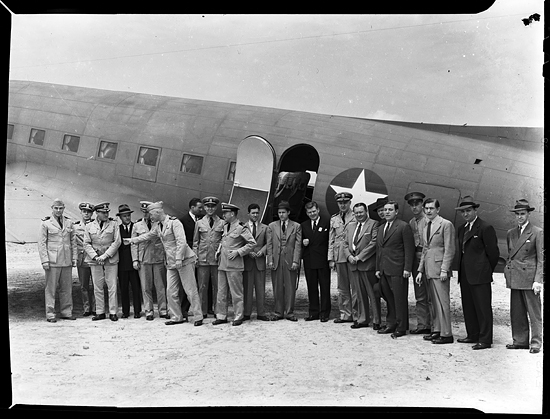 Military personnel standing next to airplane