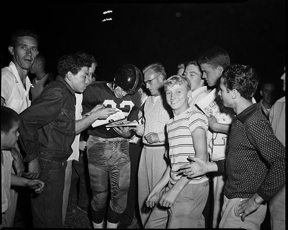 """Washington Redskins' Charlie """"Choo Choo"""" Justice signing autographs, September 11, 1954."""