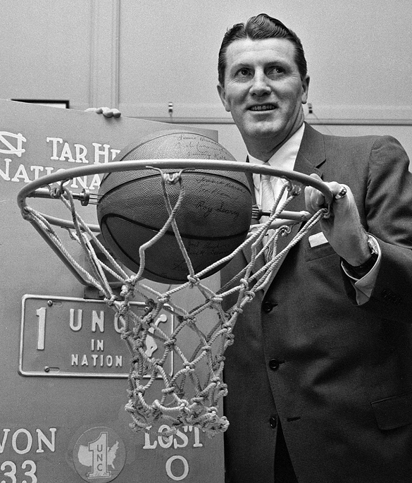 UNC men's basketball coach Frank McGuire posed with basketball hoop, net, and ball