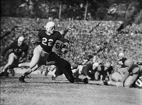 UNC-Chapel Hill tailback Charlie Justice (#22) running with ball at a UNC vs Virginia football game held in in Kenan Stadium on November 29, 1947. Also in the scene are #48 UNC Blocking Back Don Hartig, #60 Virginia Right End Robert Weir, #23 UNC Wingback Jim Camp, and #60 UNC Right Guard Sid Varney.