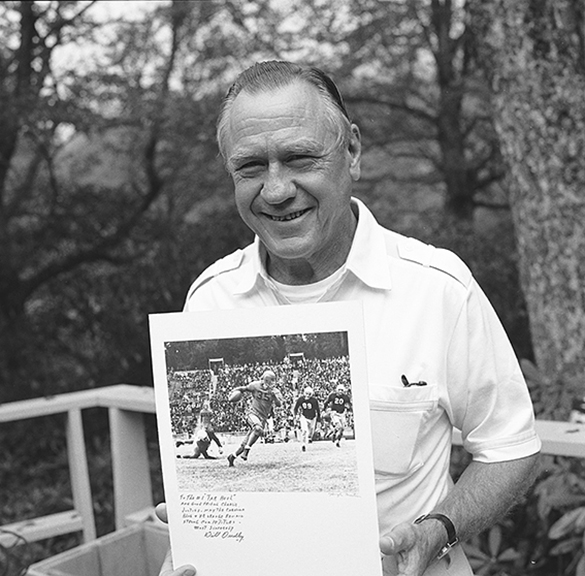 "University of Virginia All America football star ""Bullet"" Bill Dudley, holding signed print of a well-known Hugh Morton picture from the November 20, 1941, UNC-UVA football game."
