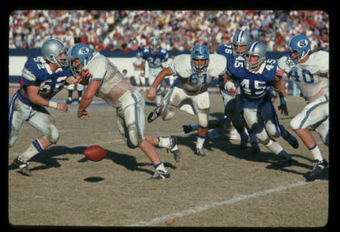 Action during the UNC-Chapel Hill vs. Duke University football game at Duke's Wallace Wade Stadium, Durham, N.C, November 24, 1973. UNC players: #61 Offensive Guard Billy Newton and #40 Halfback Jimmy Jerome. Duke players: #62 Linebacker Dave Meier, #24 Defensive Safety Buster Cox, #76 Defense Tackle John Ricca, and #45 Linebacker Keith Stoneback.