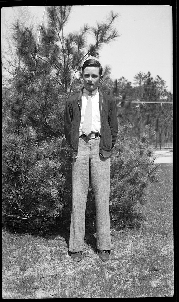 Hugh Morton as a boy, dressed in a jacket and tie, standing in front of an evergreen tree, probably in the Wilmington, NC area.