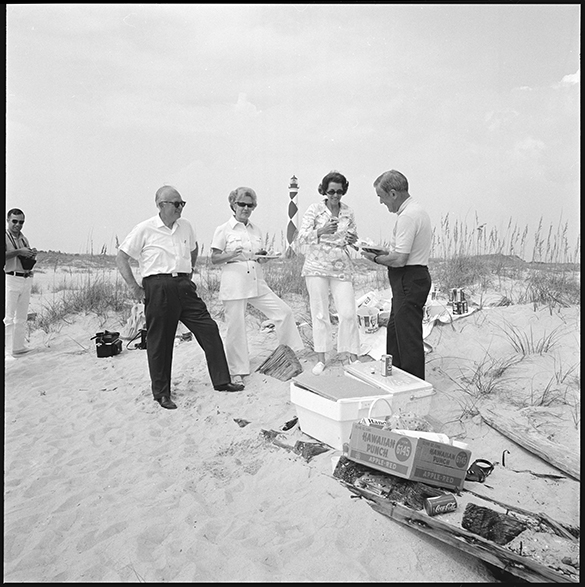 Hugh Morton (left) and Julia Morton (second from right), entertaining during a picnic on Cape Lookout, while a photographer looks on.