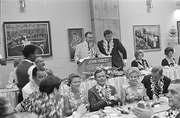 "This photograph is a non-cropped version of the version that appears in the booklet titled ""Hugh Morton's DEMOCRATIC Photo Album."" It is captioned, ""N. C. Democratic Chairman Joe Yates introduces Governor Bob Scott at the Governor's Down-East Jamboree at Atlantic Beach on September 18, 1971. At the head table at left is Maryland Governor Marvin Mandel, principal speaker. Party officials in the foreground include: Speaker Phil Godwin, YDC President Charles Winberry, Party Secretary Mrs. E. K. Powe and Mr. Powe, and Party Vice Chairman Mrs. James M. Harper and Mr. Harper."""