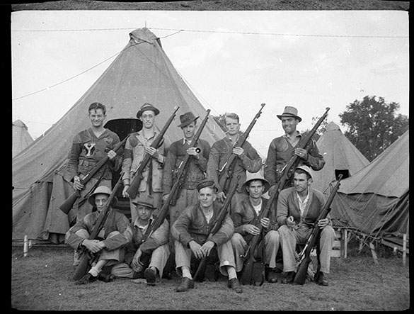 """North Carolina Rifle Team, Camp Perry, Ohio."" Hugh Morton (rear, left, with Camp Yonahnoka patch) and other young men posing with rifles."