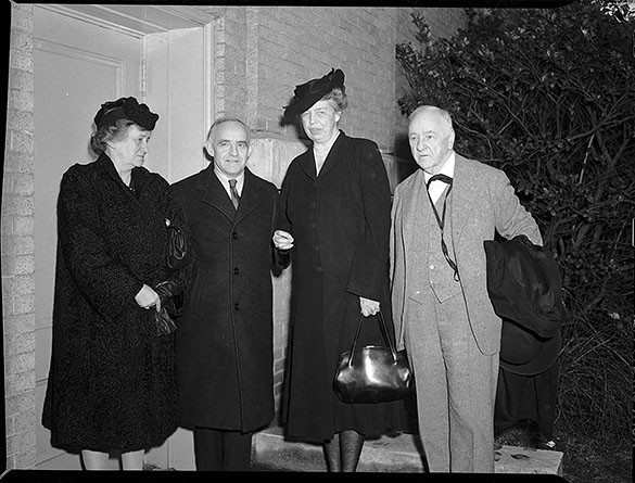 "Eleanor Roosevelt standing at the stage entrance to Memorial Hall with her secretary Malvina Thompson on the left, Frank Porter Graham (second from left), and Josephus Daniels (right), during Roosevelt's January 1942 visit to the University of North Carolina-Chapel Hill, as the keynote speaker at a jointly-sponsored International Student Service-Carolina Political Union conference on ""Youth's Stake in War Aims and Peace Plans."""