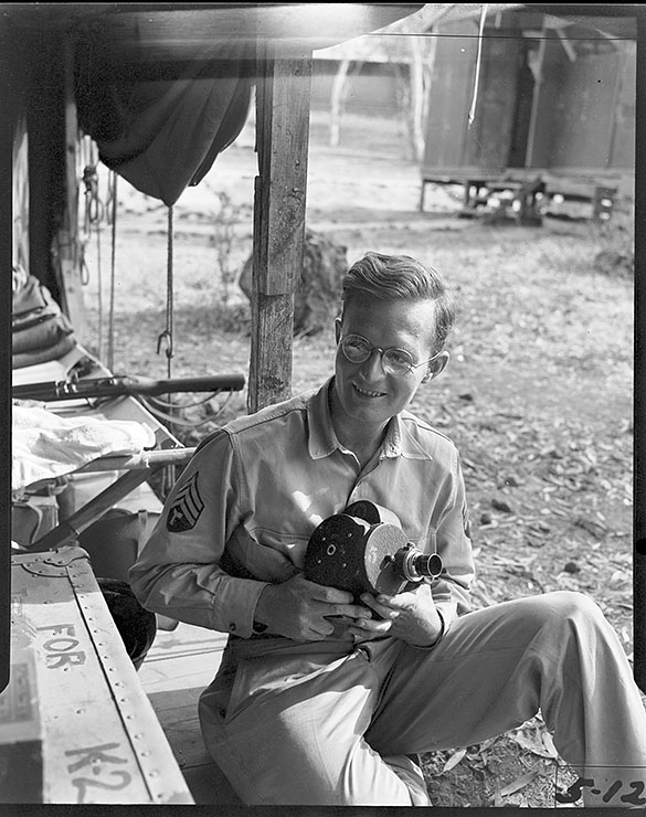 Photographer Hugh Morton at military encampment, holding movie camera. Taken during Morton's World War II service with the 161st Signal Photography Corps.