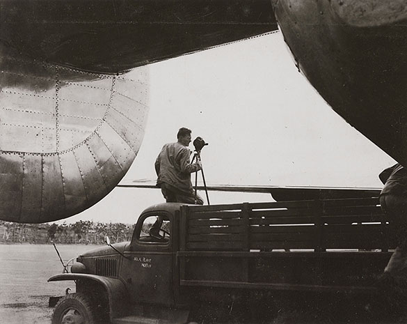 "Hugh Morton with movie camera during World War II. The writing on the truck's door appears to read ""Milk Plane Morton."""