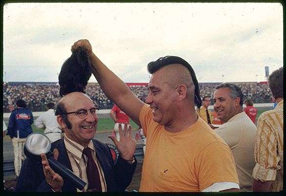 CHECKING UNDER THE HOOD—A man with a Mohawk-style haircut lifts the lid of a bald man wearing a toupee during the 1971 National 500 at the Charlotte Motor Speedway.