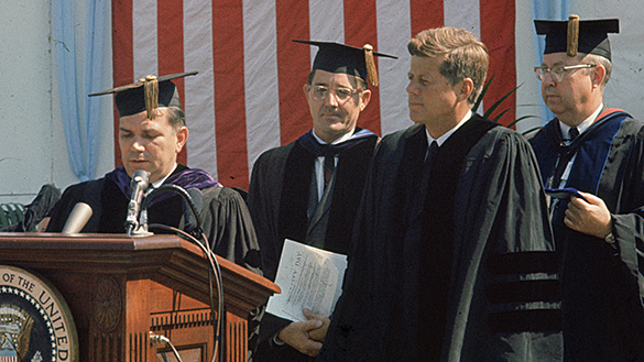 UNC Chancellor William Aycock pictured speaking at podium, with UNC System President Bill Friday, President John F. Kennedy, and Dr. James L. Godfrey at University Day, October 12, 1961, at the University of North Carolina at Chapel Hill.