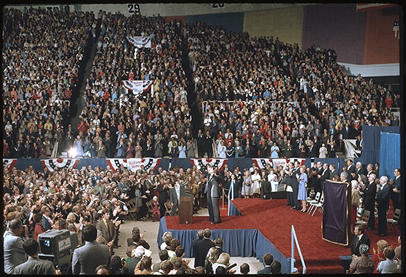 "Billy Graham and Richard M. Nixon, arm-in-arm, wave to the audience during ""Billy Graham Day,"" Charlotte Coliseum, October 15, 1971.  H. R. Haldeman appears to be next to Pat Nixon."
