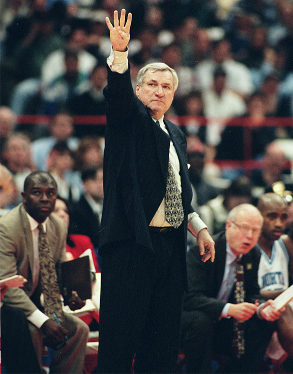 """Dean Smith signaling """"Four Corners"""" during his 879th, and last, victory as head basketball coach at UNC.  Hugh Morton photographed this scene during the Eastern Regional championship game played against Louisville at Syracuse, New York."""