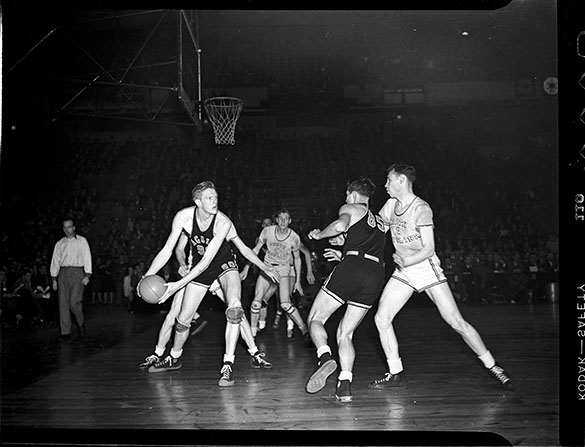 "This is one of Hugh Morton's photographs from his first NCAA Men's Basketball Tournament, the 1946 championship game between UNC and Oklahoma A&M, played in Madison Square Garden in New York City.  On the court from Oklahoma A&M are #90 Bob Kurland and #85 Sam Aubrey. From North Carolina are #4 Bob Paxton, #13 John ""Hook"" Dillon, and Bones McKinney (only arms and legs are visible).  The Aggies won 43–40."