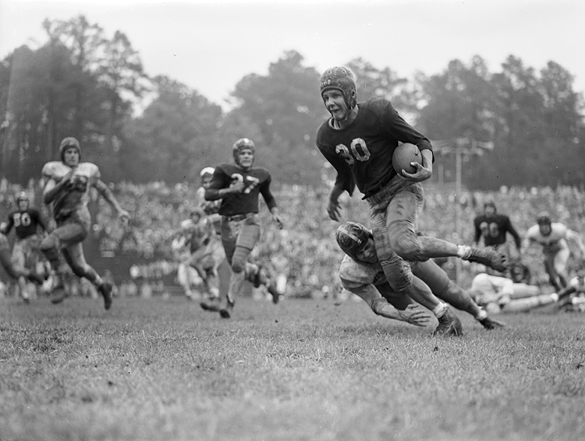 Jim Bunting (#30) carries the football within the grasp of a tackler during the UNC Blue-White game played on April 30, 1949. This photograph, cropped tightly as a vertical to focus on the runner eluding the tackler, appeared in The Charlotte News on May 2nd.