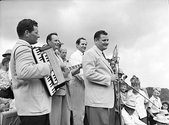 "Arthur Smith and band ""The Crackerjacks"" performing on an outdoor stage at ""Singing on the Mountain"" gospel festival, Grandfather Mountain, Linville, NC. L to R: Ralph Smith, Sonny Smith, Don Lear, Arthur Smith. Photograph illustrates article about Smith, ""Another Tar Heel Booster,"" in September 2, 1950 issue of THE STATE magazine, with caption that says Smith is ""singing his original composition, 'Foolish Questions.'"""