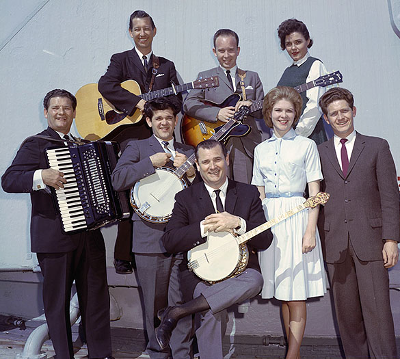 "Arthur Smith (center, with banjo), posing with his band ""The Crackerjacks."" Back Row (L to R): Tommy Faile, Wayne Haas, Kaye Murray; Front Row (L to R): Ralph Smith, Carl Hunt, Arthur Smith, Carlene ""Sam"" Howell, Jim Buchanan. Possibly taken on the deck of the USS North Carolina in Wilmington, N.C."