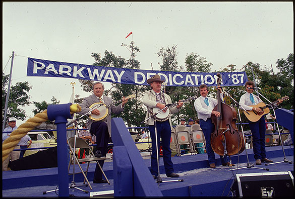 Musicians Arthur Smith (far left), Raymond Fairchild (second from left), and others performing at the dedication of the final piece of the Blue Ridge Parkway, Grandfather Mountain, N.C.