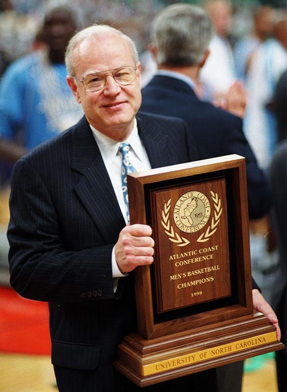 UNC Head Coach Bill Guthridge holding trophy after UNC-Chapel Hill beat Duke University in finals of ACC tournament, Greensboro Coliseum, Greensboro, N.C., on March 8, 1998.