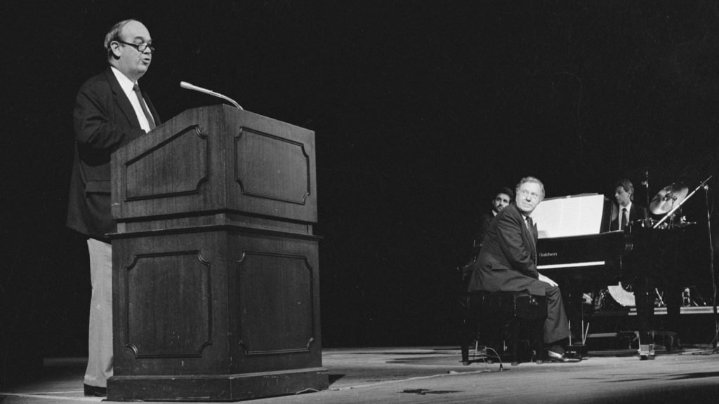 Charles Kuralt, Loonis McGlohon, and musicians onstage at the Stevens Center in Winston-Salem, NC during a performance of Kuralt and McGlohon's collaborative album of music, narration, and folklore titled North Carolina is My Home.
