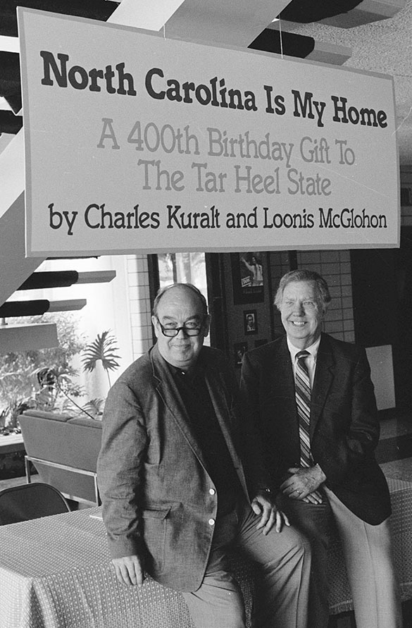 Charles Kuralt (left) and Loonis McGlohon posing under sign in Charlotte's Ovens Auditorium at unknown date.
