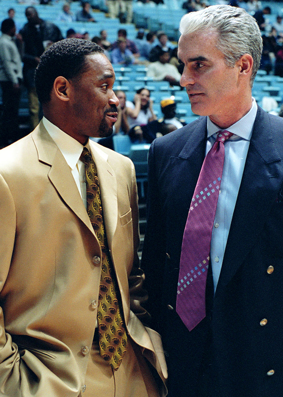 Curtis Hunter and Matt Doherty, teammates on the UNC 1982-83 and 1983-84 basketball teams, chat as coaches before their teams—North Carolina Agricultural and Technical State University and University of North Carolina at Chapel Hill—faced off on February 18, 2003 at UNC's Smith Center.  Another photograph of the former Tar Heels talking court-side can be found in the online collection of Morton photographs.