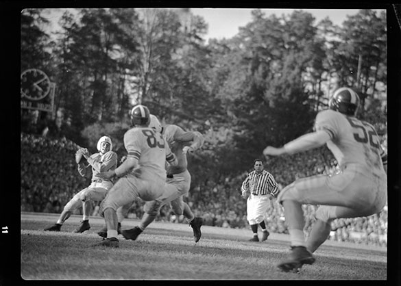 1948: #22 UNC tailback Charlie Justice, back to pass; #83 Duke left end Bill Duncan; and #52 Duke center Tommy Harris; at UNC-Chapel Hill's Kenan Stadium. Photograph, tightly cropped on Justice and Duncan, appears in the CHARLOTTE NEWS, 22 November 1948.
