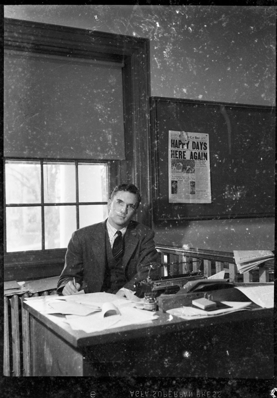 "1940: UNC-Chapel Hill student at desk at office of DAILY TAR HEEL(?). November 17, 1940 issue of THE DAILY TAR HEEL on wall in background with headline that reads ""Happy Days Here Again,"" referring to 6-3 upset victory of UNC football team over Duke University."