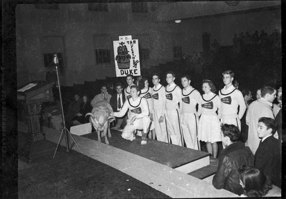 "PROBABLY 1940: UNC-Chapel Hill cheerleaders and ram mascot ""Rameses"" at indoor event, probably the pep rally before the Duke-UNC football game. Both this photograph and a similar photograph (cropped) appear in the 1941 YACKETY YACK yearbook."