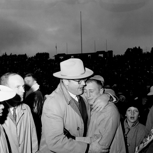 "1957: UNC Head Coach Jim Tatum (left) embraces player Dave Reed (right) after UNC-Chapel Hill versus Duke University football game at Duke Stadium, Durham, NC. ""Carolina football coach Jim Tatum (left) suspended his co-captain and star running back Dave Reed the week before UNC's 1957 game with Duke for an infraction of team rules, and consequently Carolina was very much the underdog for the game with its traditional rival. When the Tar Heels upset the Blue Devils 21 to 13, a tearful Dave Reed embraced his disciplinarian coach in the center of the field at Wallace Wade Stadium."""