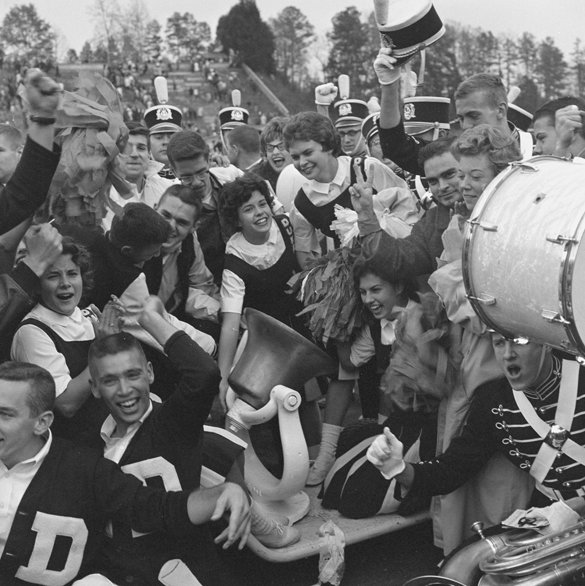 1950s or EARLY 1960s?: Duke University cheerleaders and marching band celebrating with Victory Bell after football game.