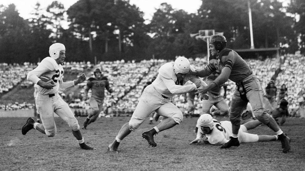 Hugh Morton photograph made during the University of North Carolina versus Virginia Polytechnic Institute football game played on September 28, 1946. #23 UNC wingback Jim Camp (#23) runs with the ball while VPI tackle John Maskas (#56) looks on from behind the play. (Photograph cropped by editor.)