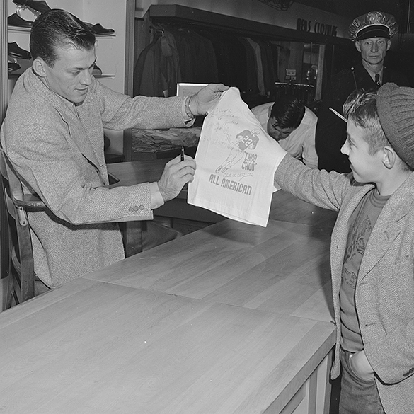 "Charlie ""Choo-Choo"" Justice autographing a T-shirt at J. C. Penny's department store, Burlington, N. C. , on 11 January 1950. Photograph by Edward J. McCauley, cropped by blog editor."