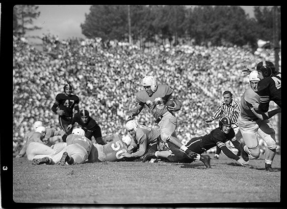 UNC Wing Back Johnny Clements (#20) running with ball against Wake Forest. UNC Left End Art Weiner (#50) on ground.
