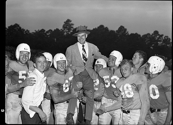 UNC football players celebrating their win over Texas. Head Coach Carl Snavely is being lifted by UNC's Art Weiner #50; UNC Hosea Rodgers #70; UNC Dan Stiegman #67; UNC Charlie Justice #22; UNC Kenny Powell #53; UNC Don Hartig #48. The two players on the far right are Bob Cox (without a helmet) and #20 Johnny Clements. The Charlotte News published this photograph on September 27th.
