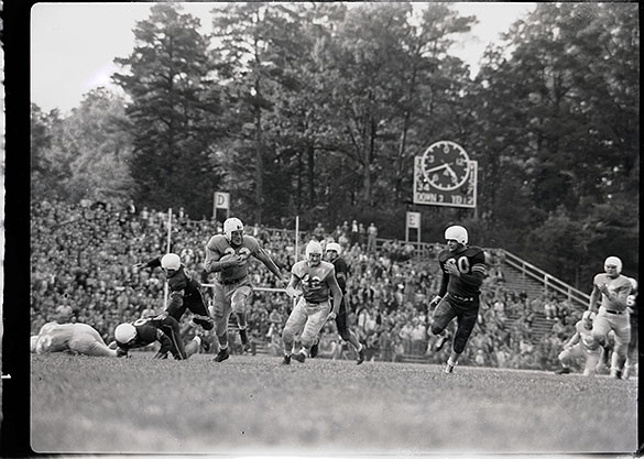 "Louisiana State University vs. UNC-Chapel Hill at Kenan Memorial Stadium. Often-published photo of Charlie ""Choo Choo"" Justice running with the football. UNC won 34-7. UNC players (other than Charlie Justice #22 with the ball): #33 Blocking Back Bobby Weant (on the ground far left), #36 Right Guard Bill Slate, #32 Wingback Merl Norcross, #42 Left Guard Bob Mitten. LSU players: #60 Guard Gerald Reynolds, #83 End Melvin ""Sam"" Lyle"